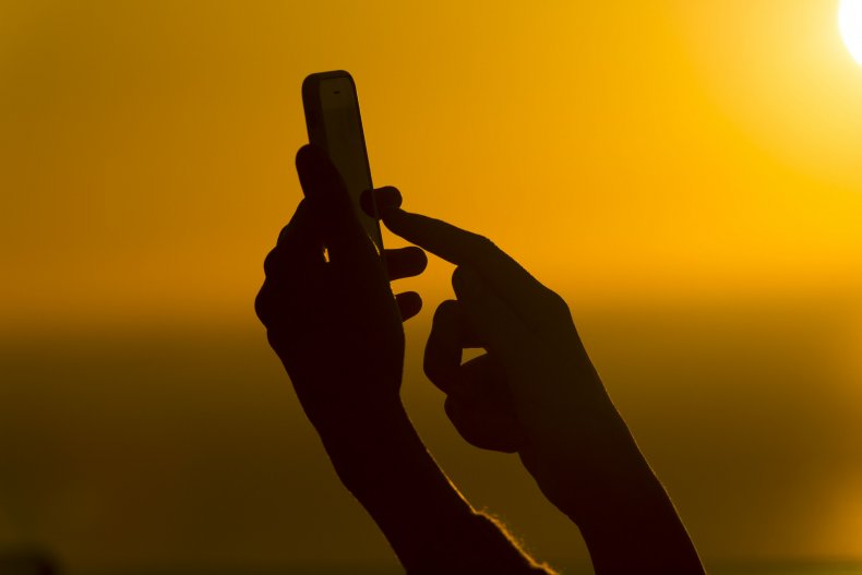 Silhouetted woman holding a mobile phone