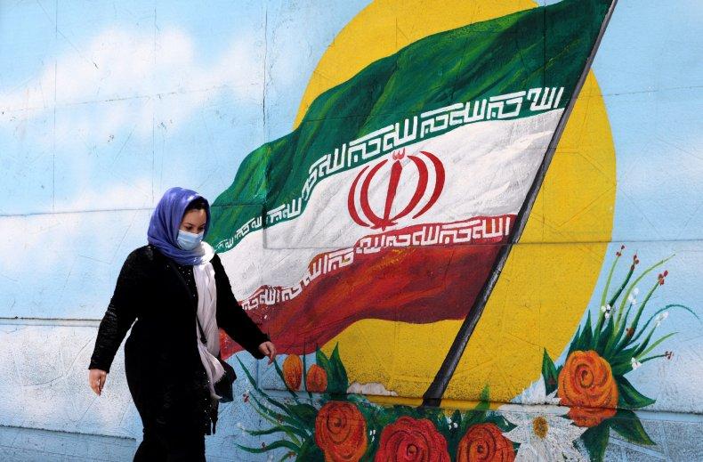 An Iranian woman walks past a mural