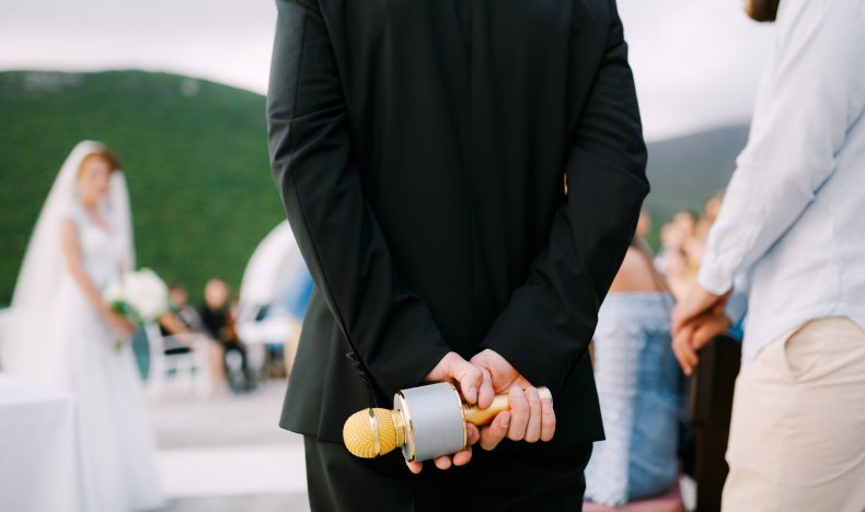 Man holds microphone behind back at wedding