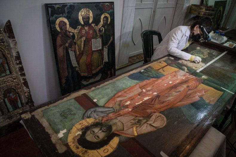 Restoration assistant Asli Erel cleans icon