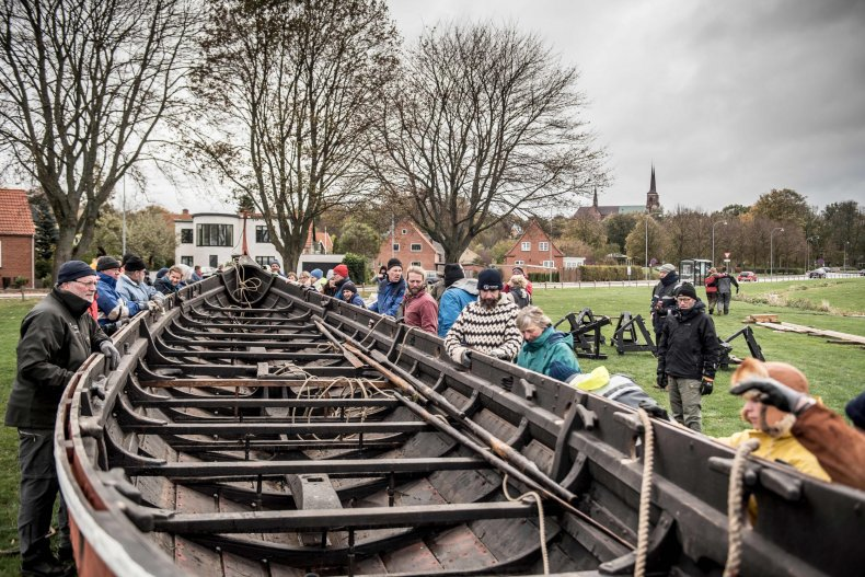 People handle a reconstructed Viking longship.