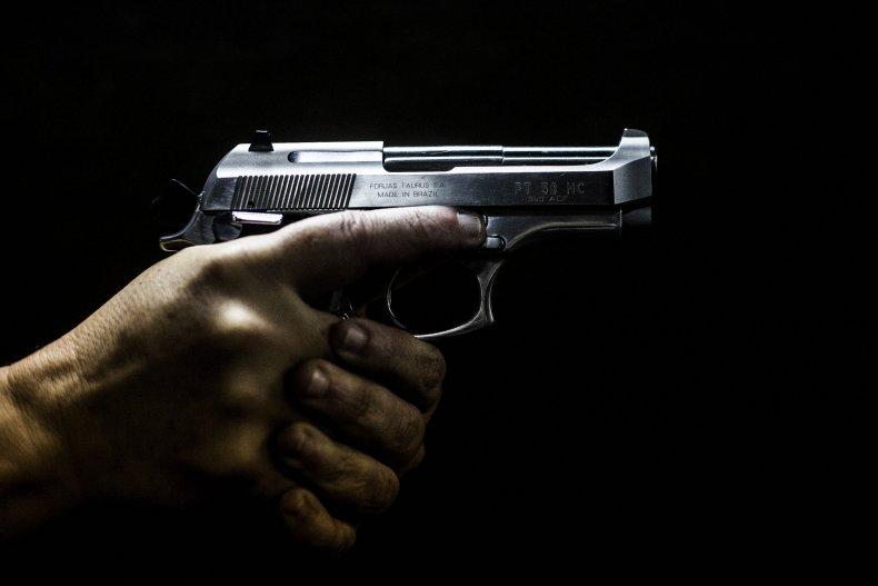 A man grips a gun in Brazil.