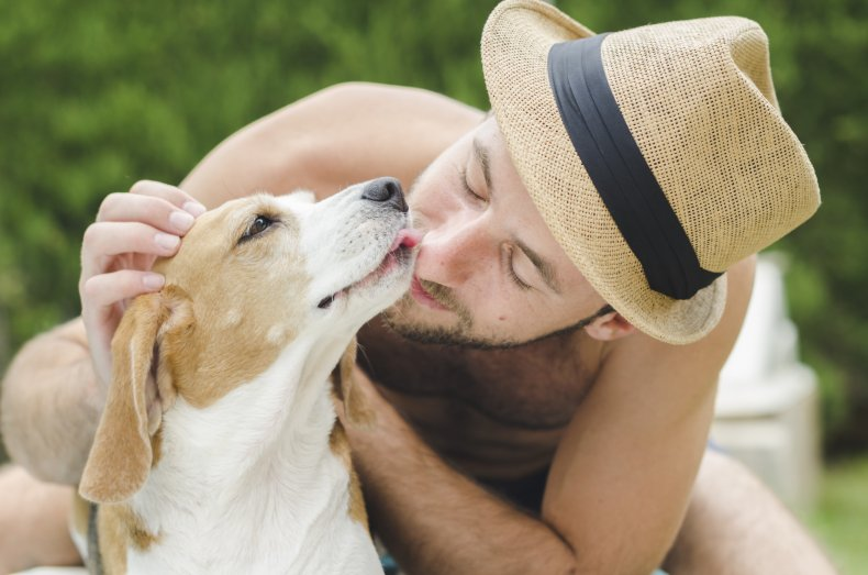 A man being kissed by his dog.
