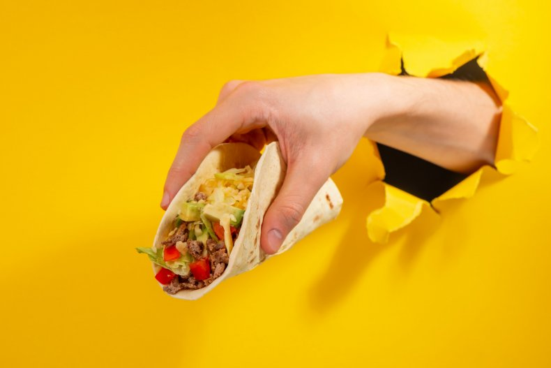 File image of a hand holding tacos.