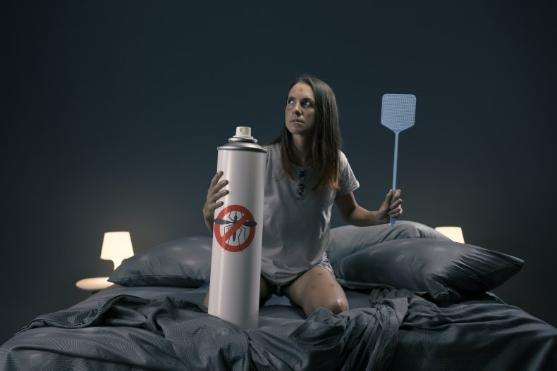 Woman swatting bugs in bed