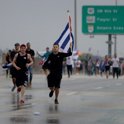 Protester runs with Cuban flag on highway