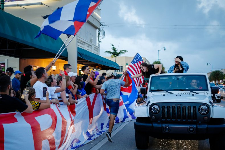 People wave US and Cuban flags during