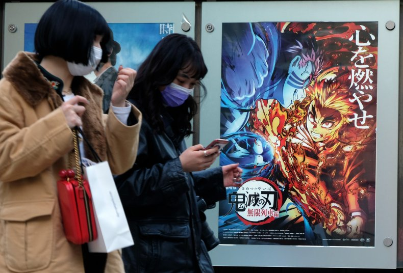 People walk past a Demon Slayer poster.