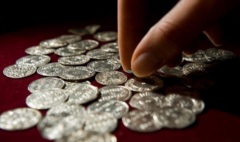 A person handles silver Viking-era coins.