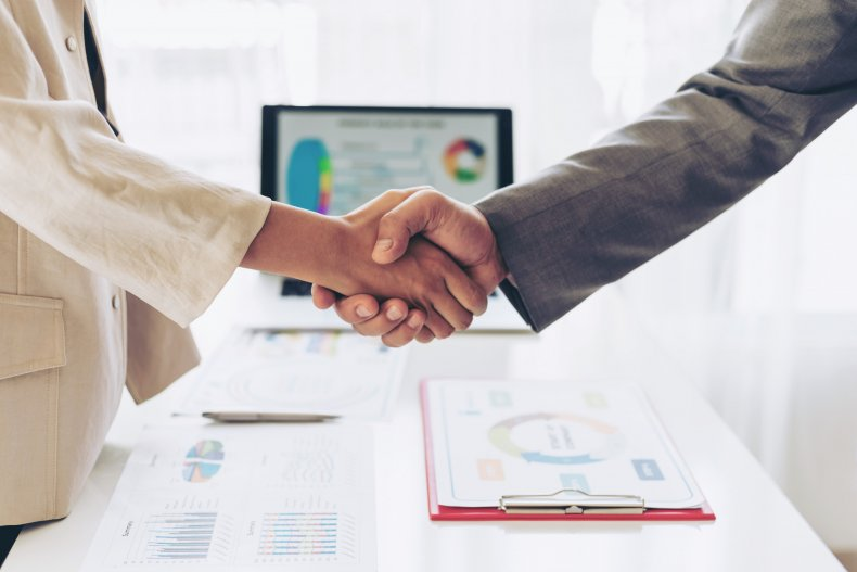 People shaking hands at a meeting.
