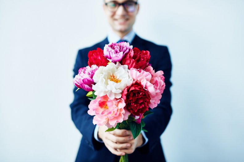 Stock image of a man holding flowers.