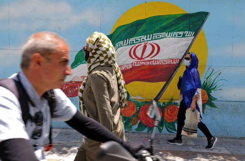 Iranians walk past a mural in Tehran