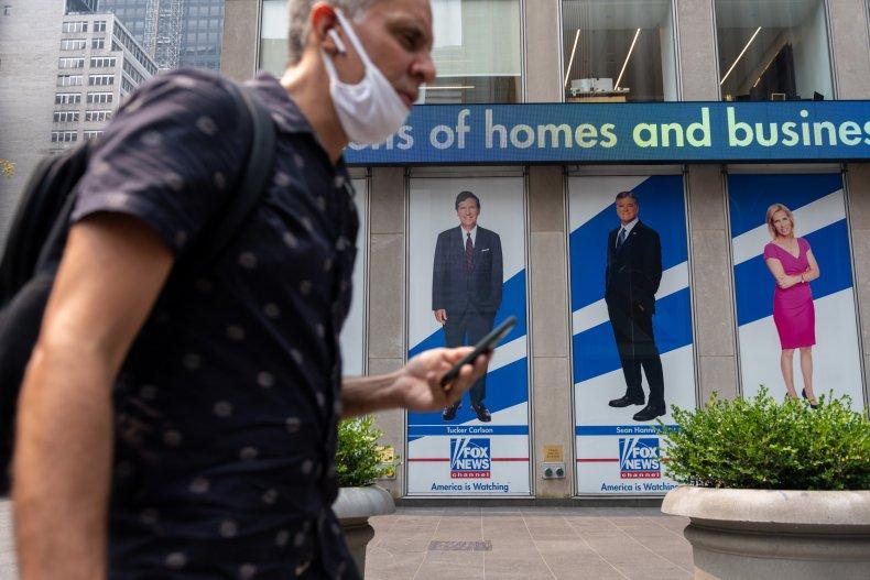 Man walks past Fox News signs