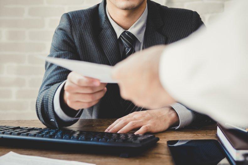 Man working at desk handed paper.