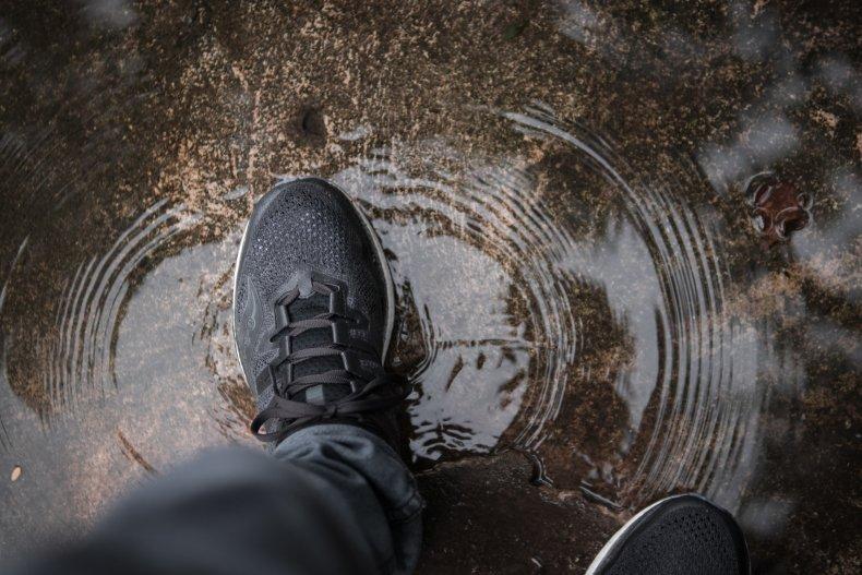 Man walking through puddle