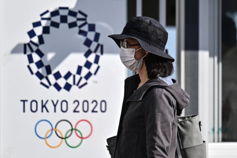 A woman near a Tokyo 2020 poster.