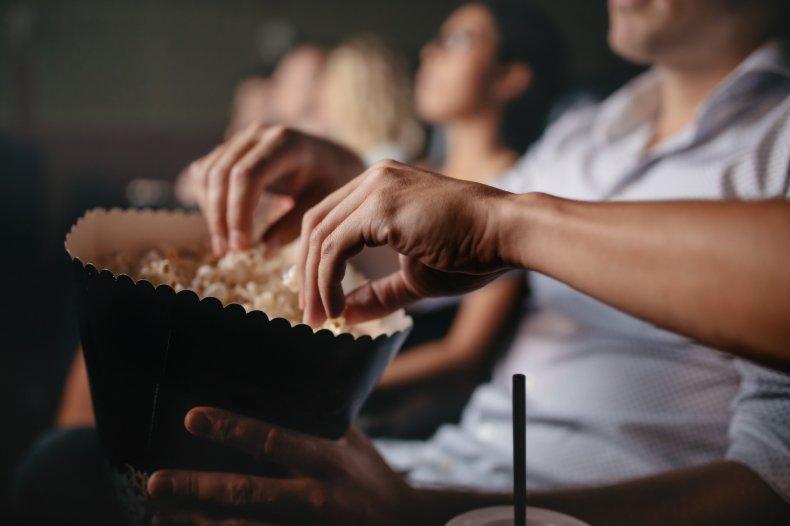 Hands in a popcorn bucket