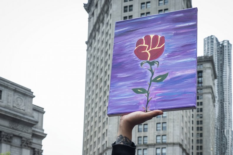 A protester carries a hand painted picture