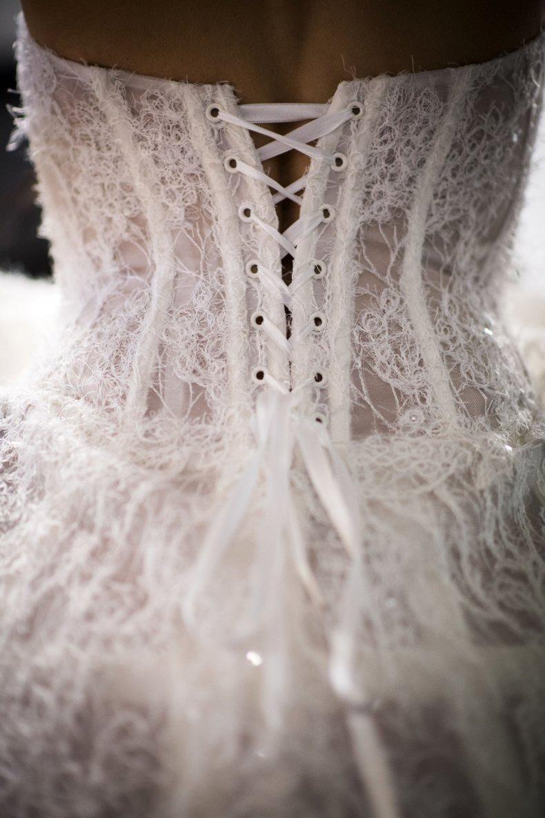 A bride wears a wedding dress.