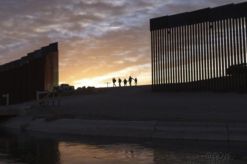 Migrant Families Pass Through Border Wall