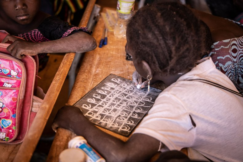 A primary schoolgirl writes on her board