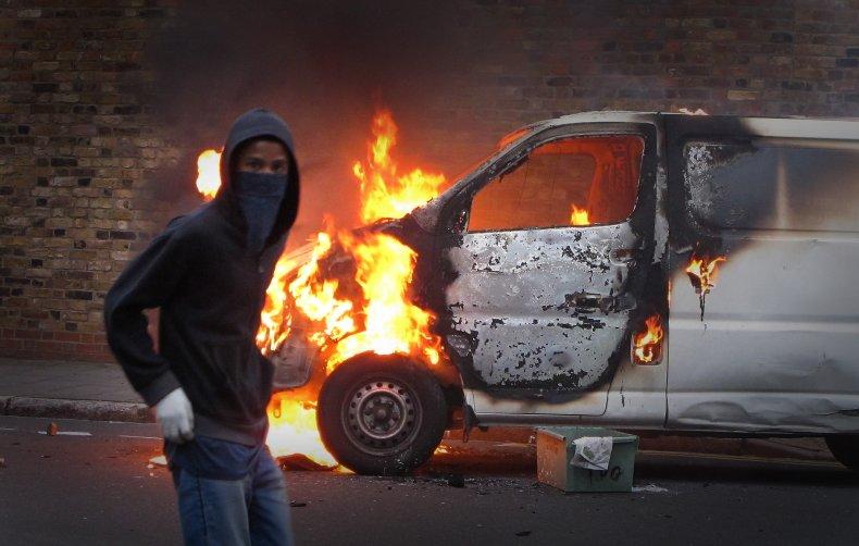 Rioter stands next to burning van