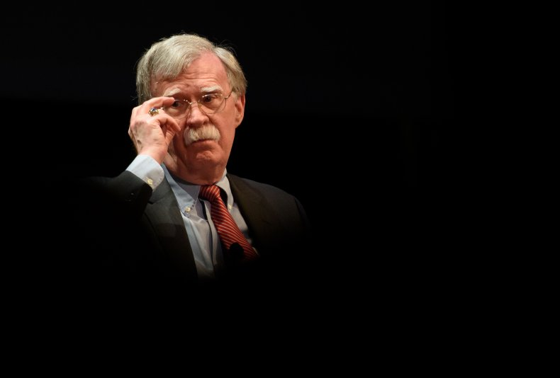 John Bolton touches his glasses while onstage.