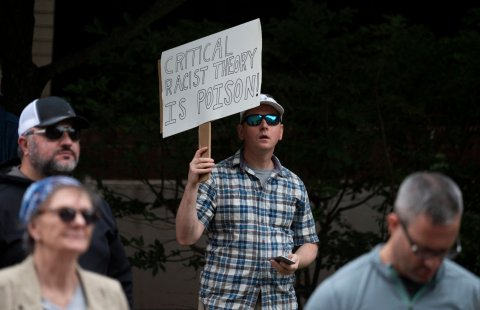 critical race theory protester holding sign