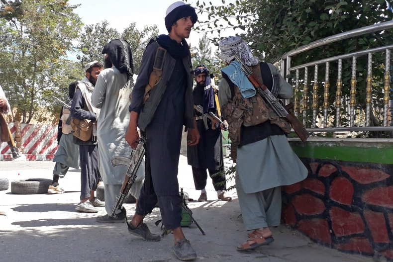 Taliban fighters stand along the roadside.