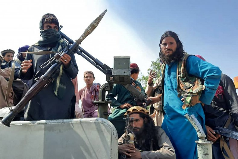 Taliban fighters sit over a vehicle.