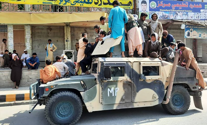 Taliban fighters sit atop Afghan army vehicle