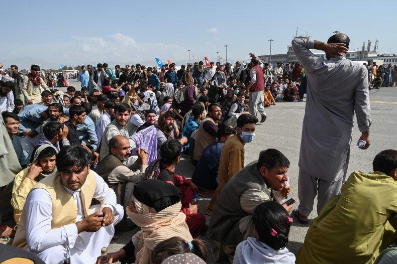 Afghan passengers sit in Kabul Airport