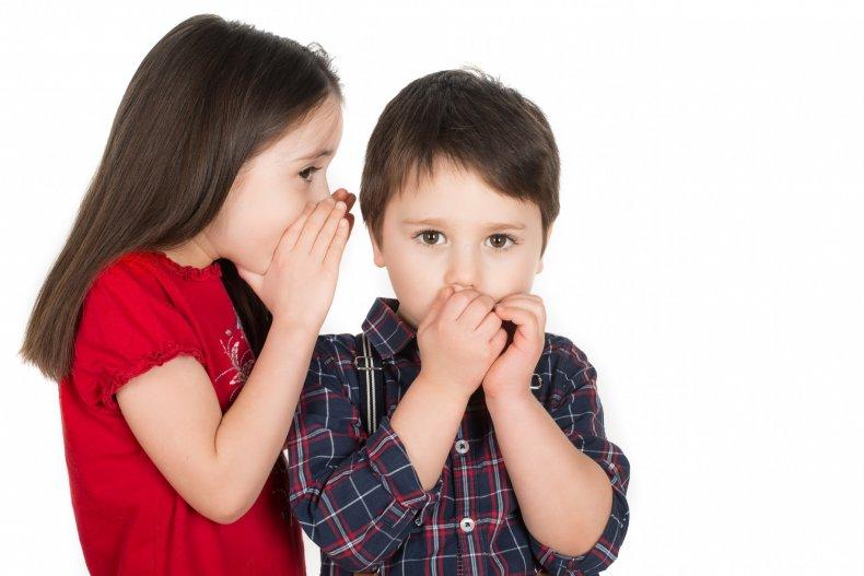 Girl whispering in boy's ear