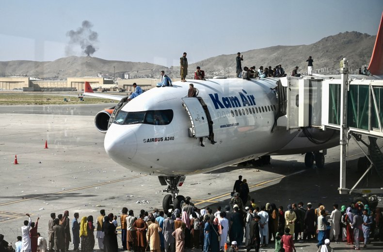 Afghan people climb atop plane