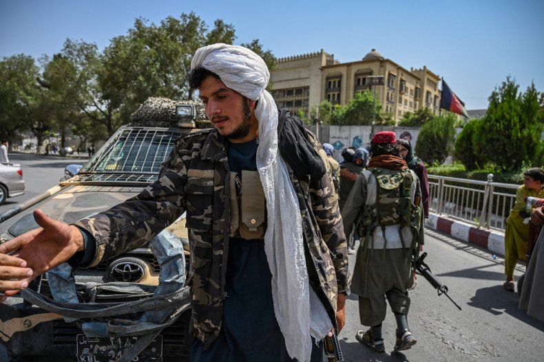 Taliban fighters stand guard along a street