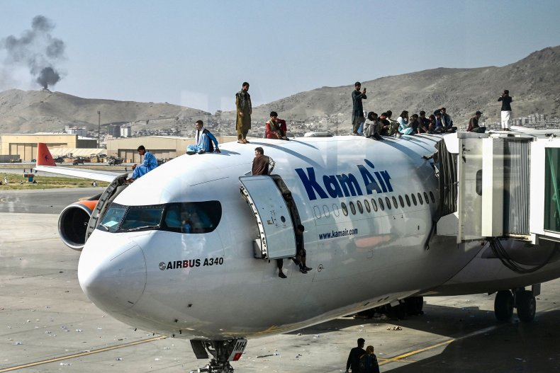 Afghan people climb a plane to flee