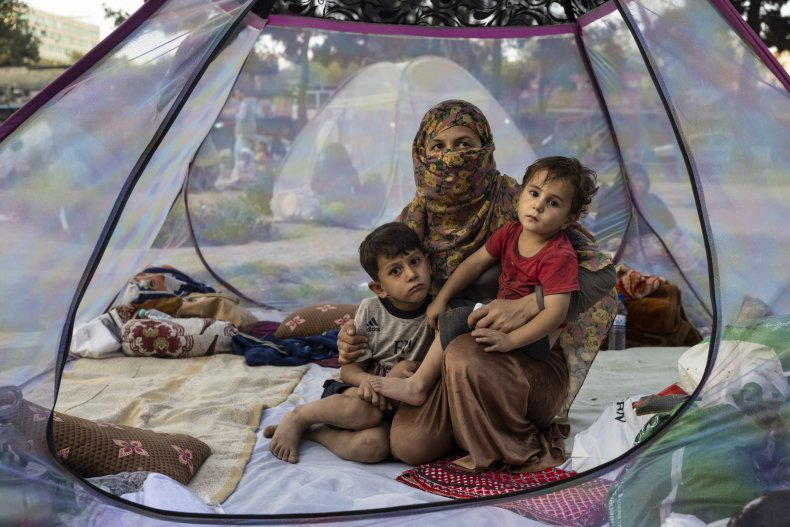 Displaced Afghan family sit in a tent