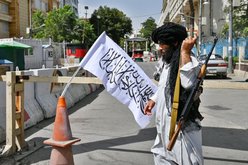 Taliban fighter at Kabul checkpoint with flag