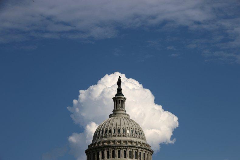 A cloud rises behind the U.S. Capitol