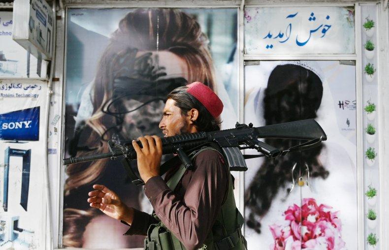 A Taliban fighter walks past a beauty