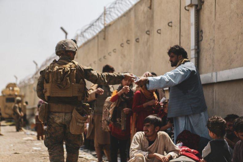 U.S. Marines handing water to Afghan evacuees.