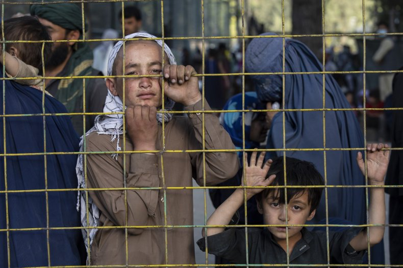 Displaced Afghans look through a fence