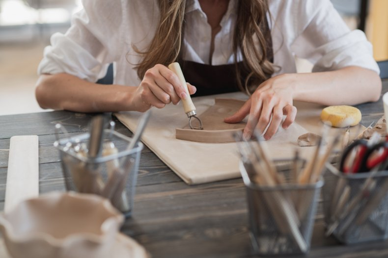 Artist working with clay in studio