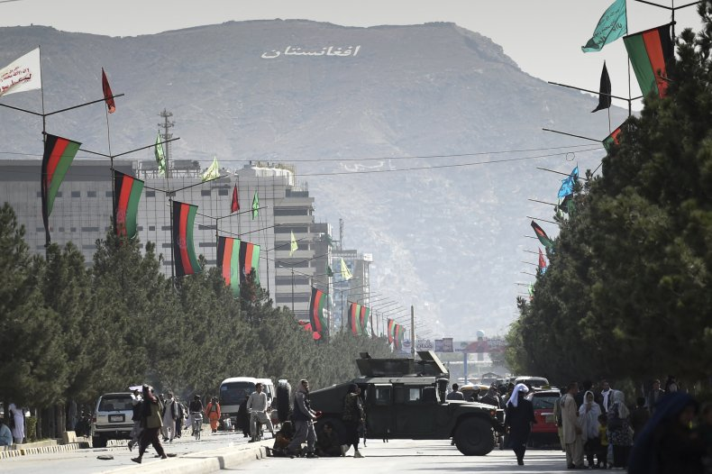 Taliban fighters block a road with Humvee