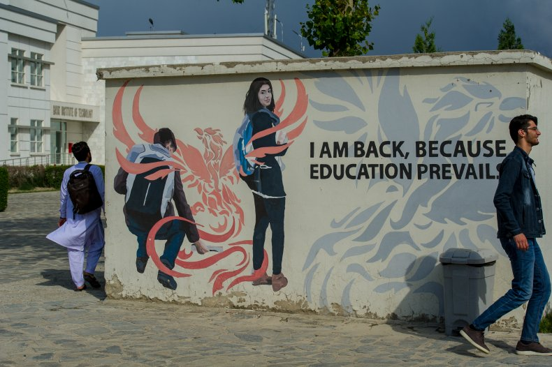 Afghan students walk by a mural
