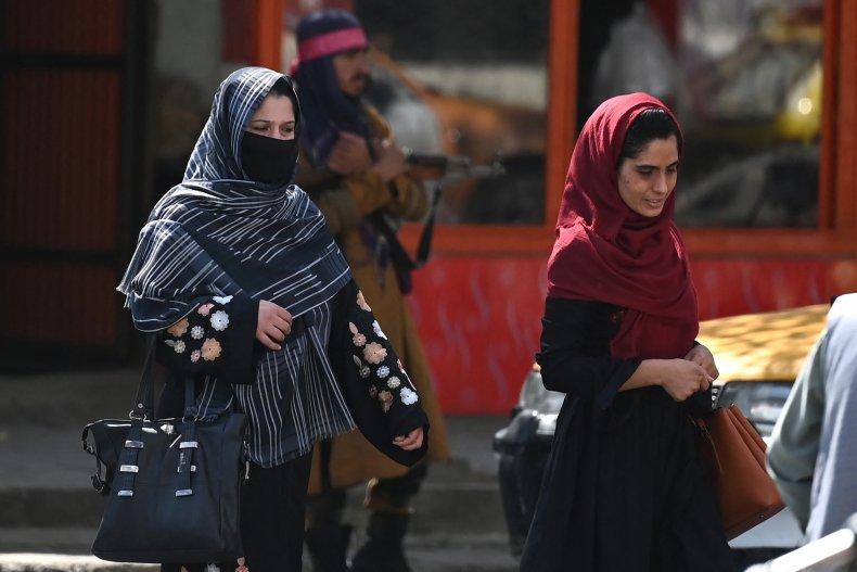 Afghan women walk past a Taliban fighter