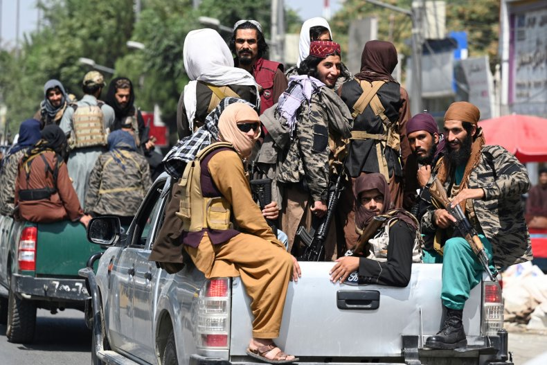 Taliban fighters patrol on vehicles