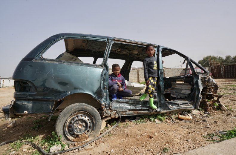 Children pose in a destroyed car