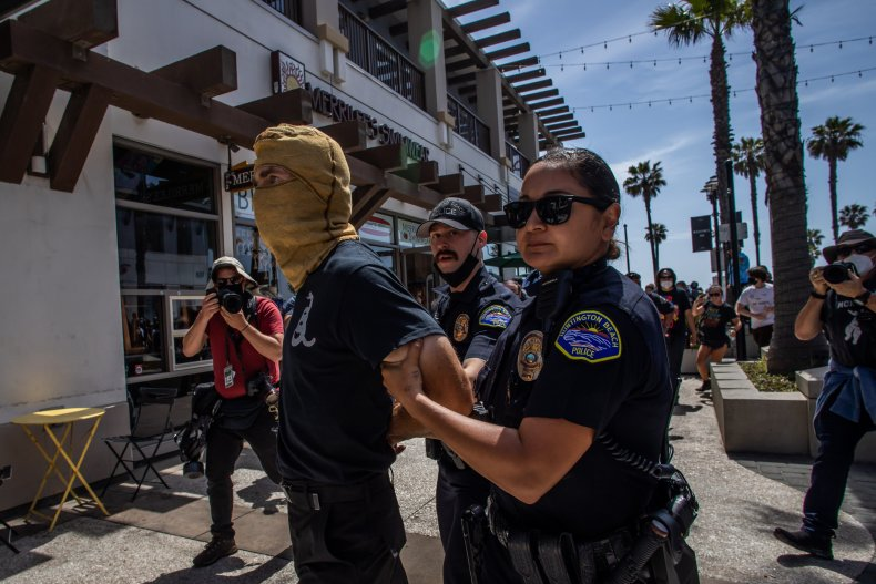 Police officers detain a Proud Boy member