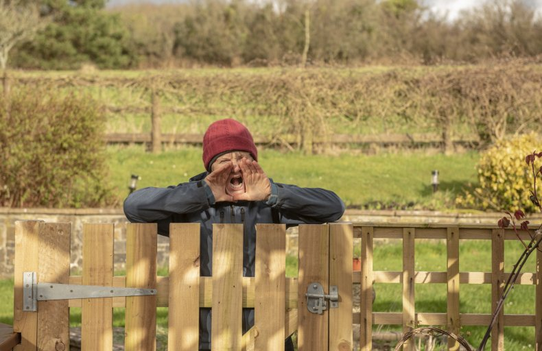 An elderly woman shouting over a fence.